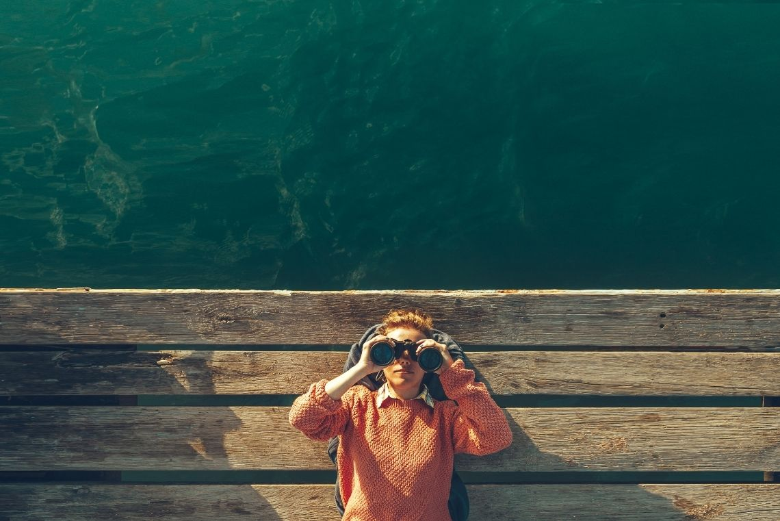 searching for happiness, a woman is looking through binoculars looking metaphorically for happiness and contentment